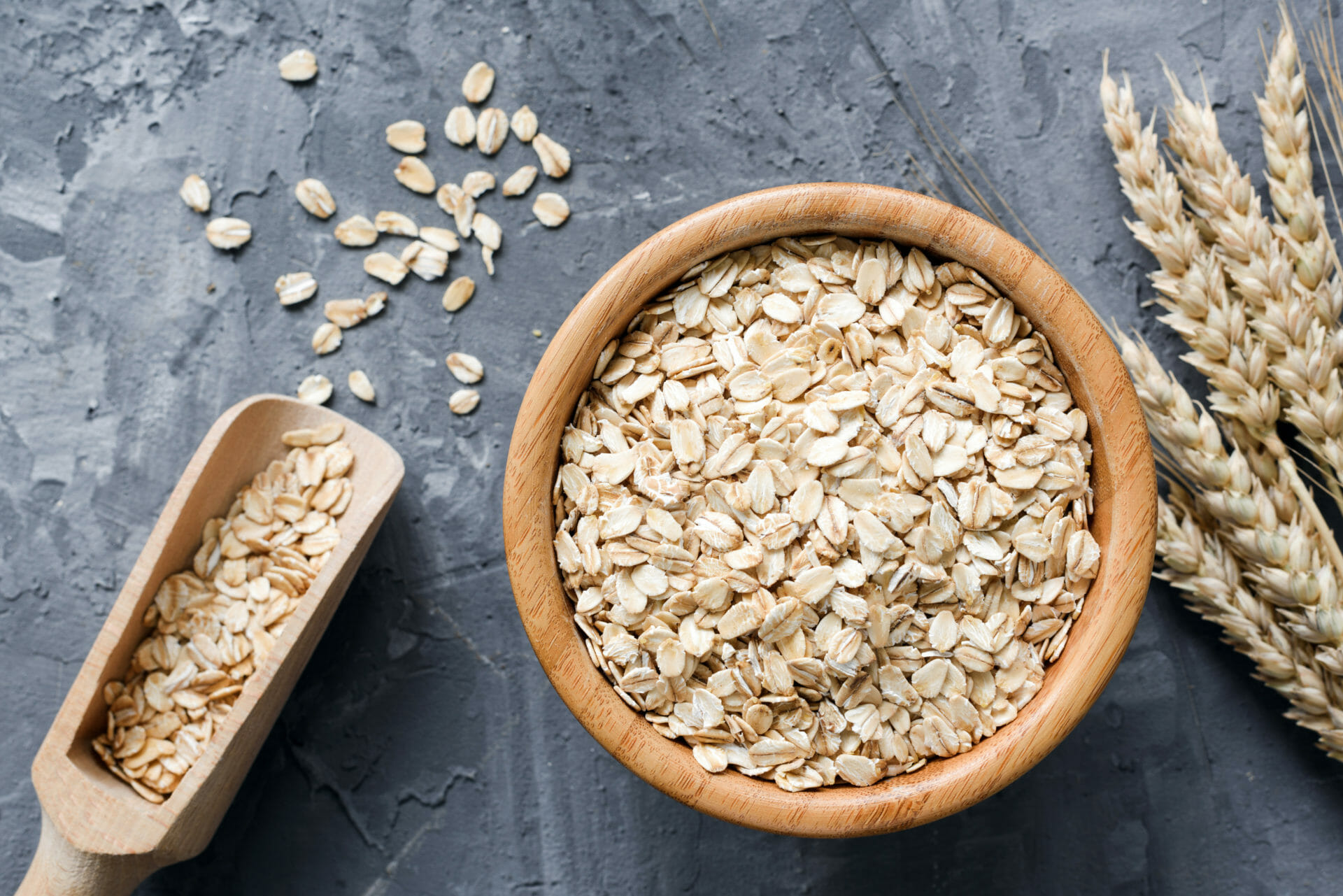 Rolled oats or oat flakes in wooden bowl and golden wheat ears