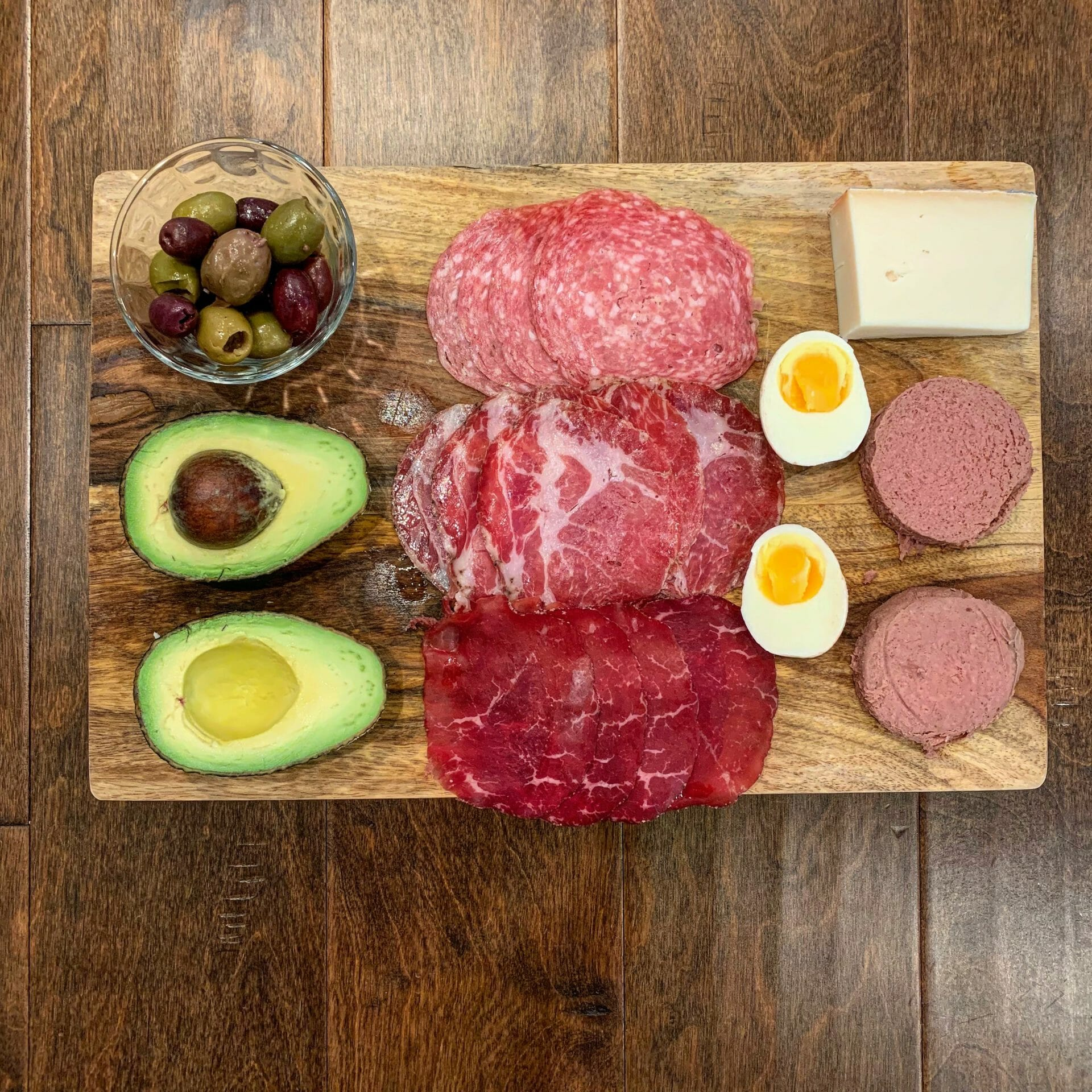 Dinner plate with uncured cold cuts, avocado, olives, goat cheese, boiled egg and pastured liverwurst