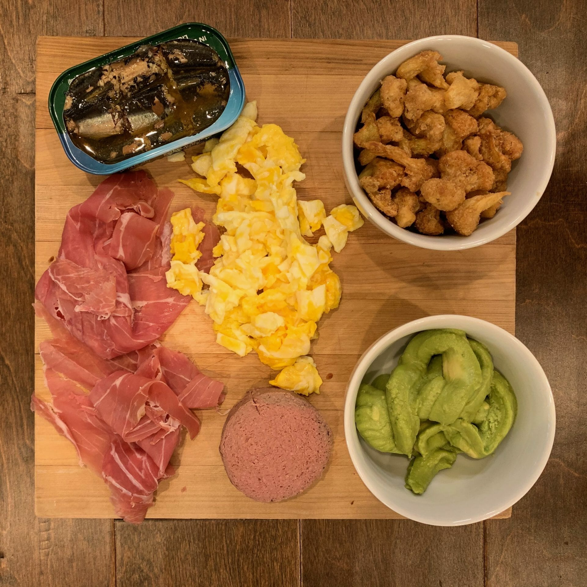 Dinner plate with canned sardines, uncured prosciutto, guacamole, liverwurst, scrambled eggs and cauliflower bites