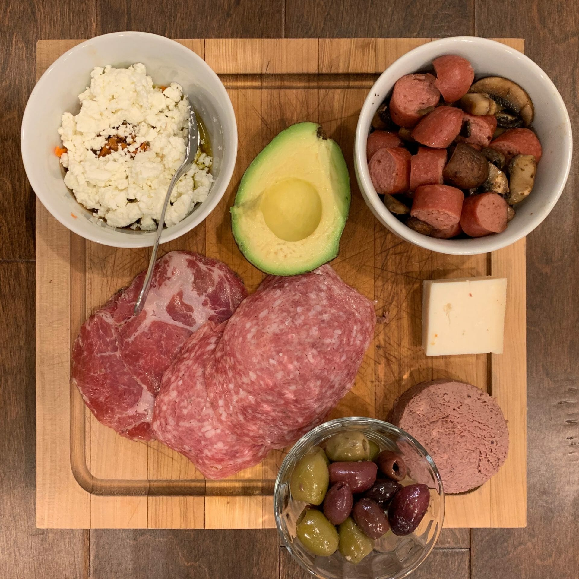 Dinner plate with uncured cold cuts, liverwurst, olives, sausages, goat cheese, mushrooms and a mix of goat cheese crumbles with carrots and a lot of olive oil