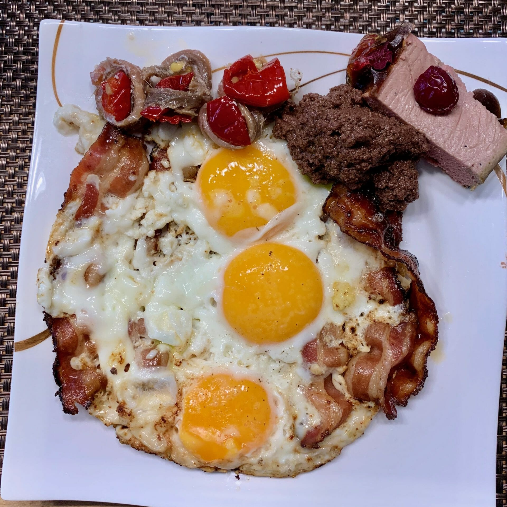 Fried eggs with pate, olive paste, anchovies and bacon
