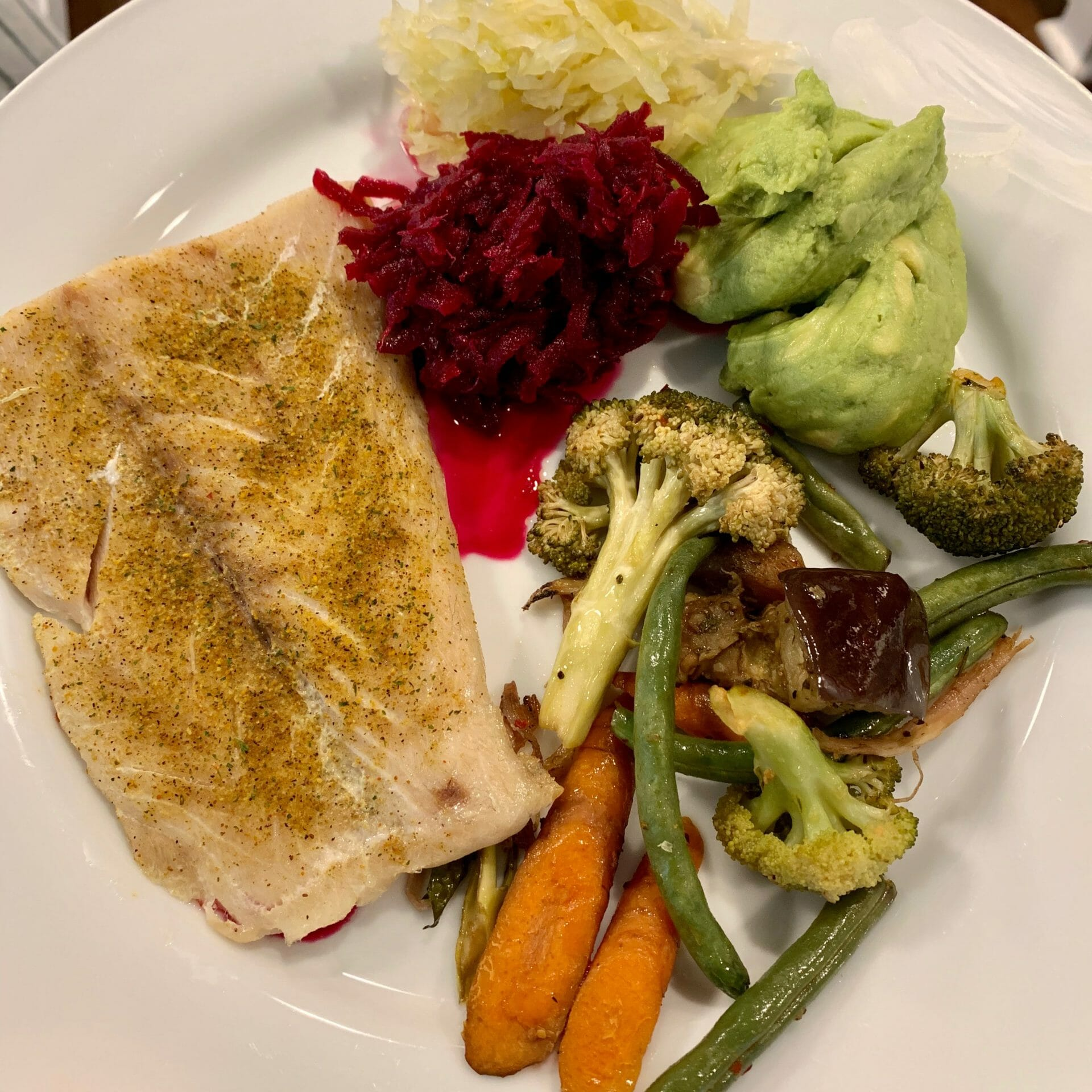 Steamed fish with carrots, broccoli, green beans, eggplant, sauerkraut, fermented beets and guacamole