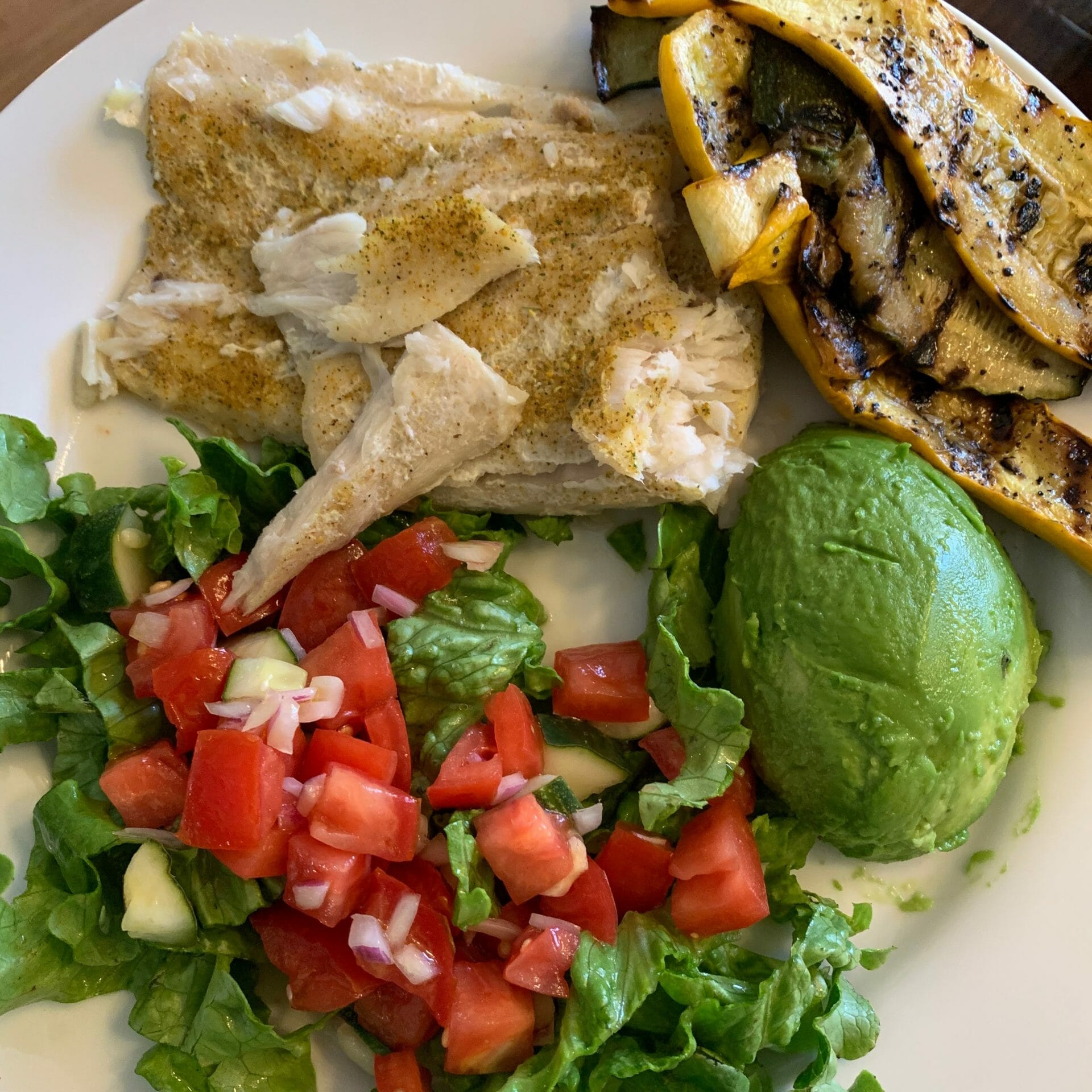 Steamed fish with grilled zucchini, avocado, lettuce, tomatoes, cucumber and onions