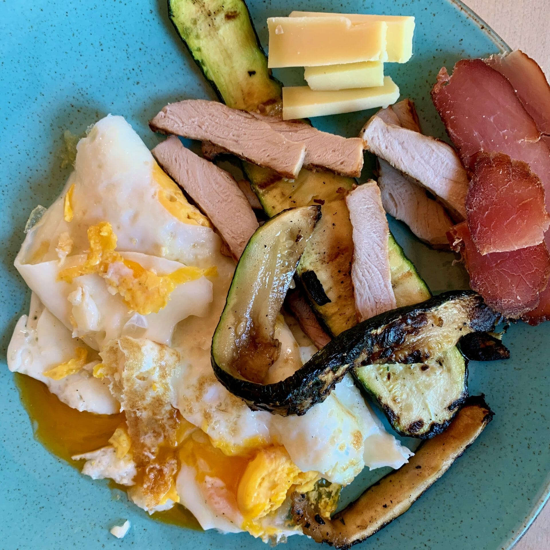 Fried eggs, ham, sliced grilled chicken, grilled zucchini and raw cheese