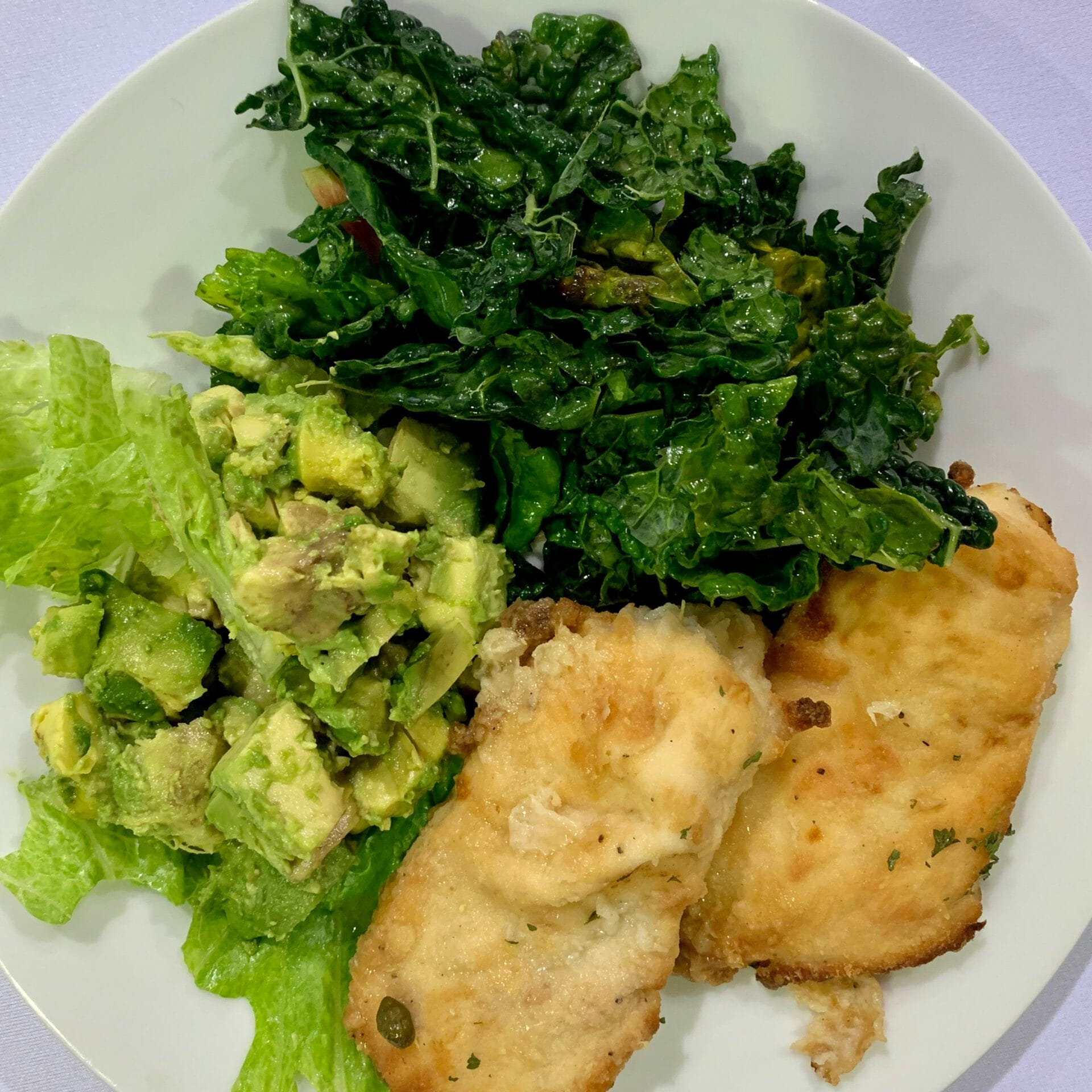 Fried fish with kale, lettuce and avocado