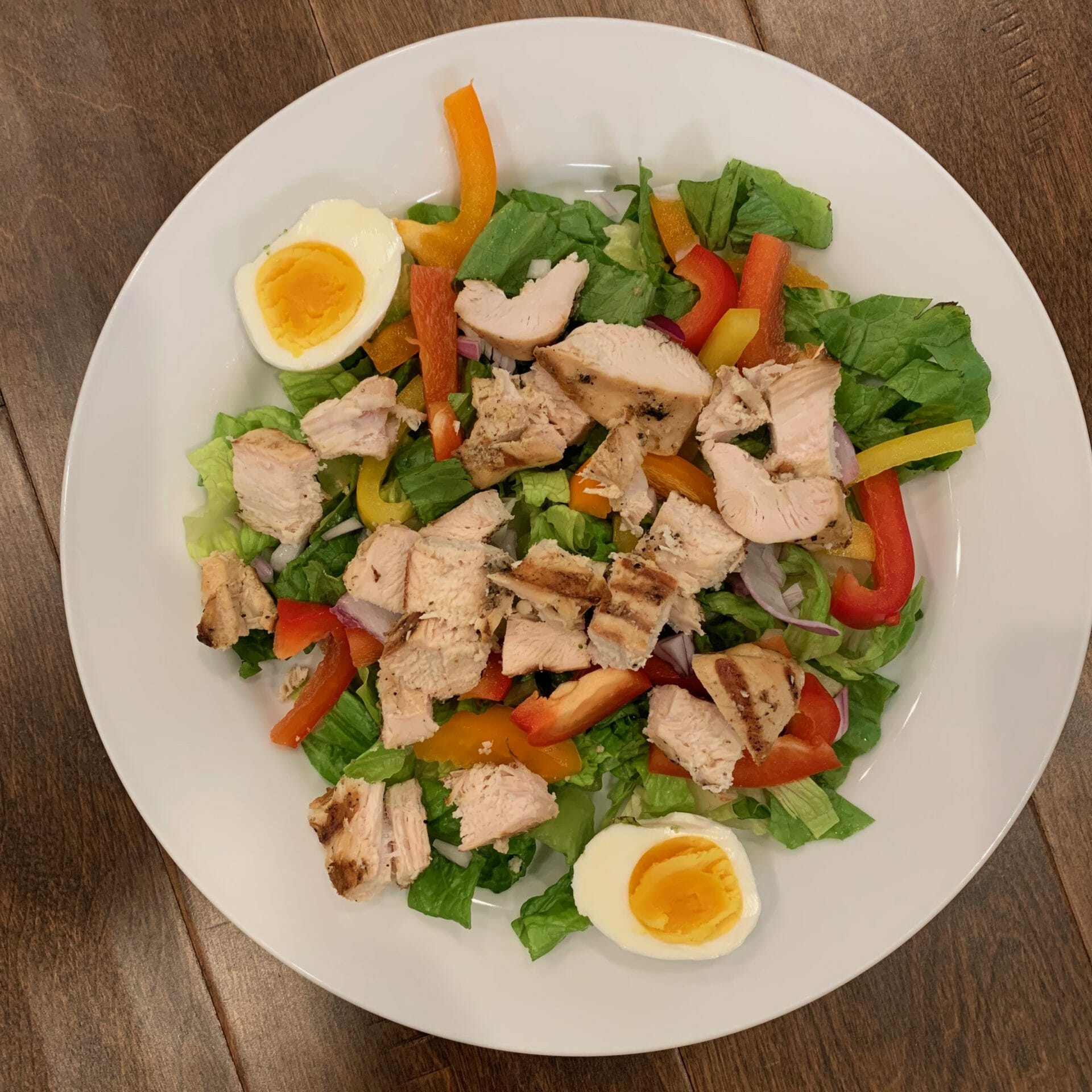 Salad with chunks of grilled chicken, lettuce, boiled eggs, peppers and onions