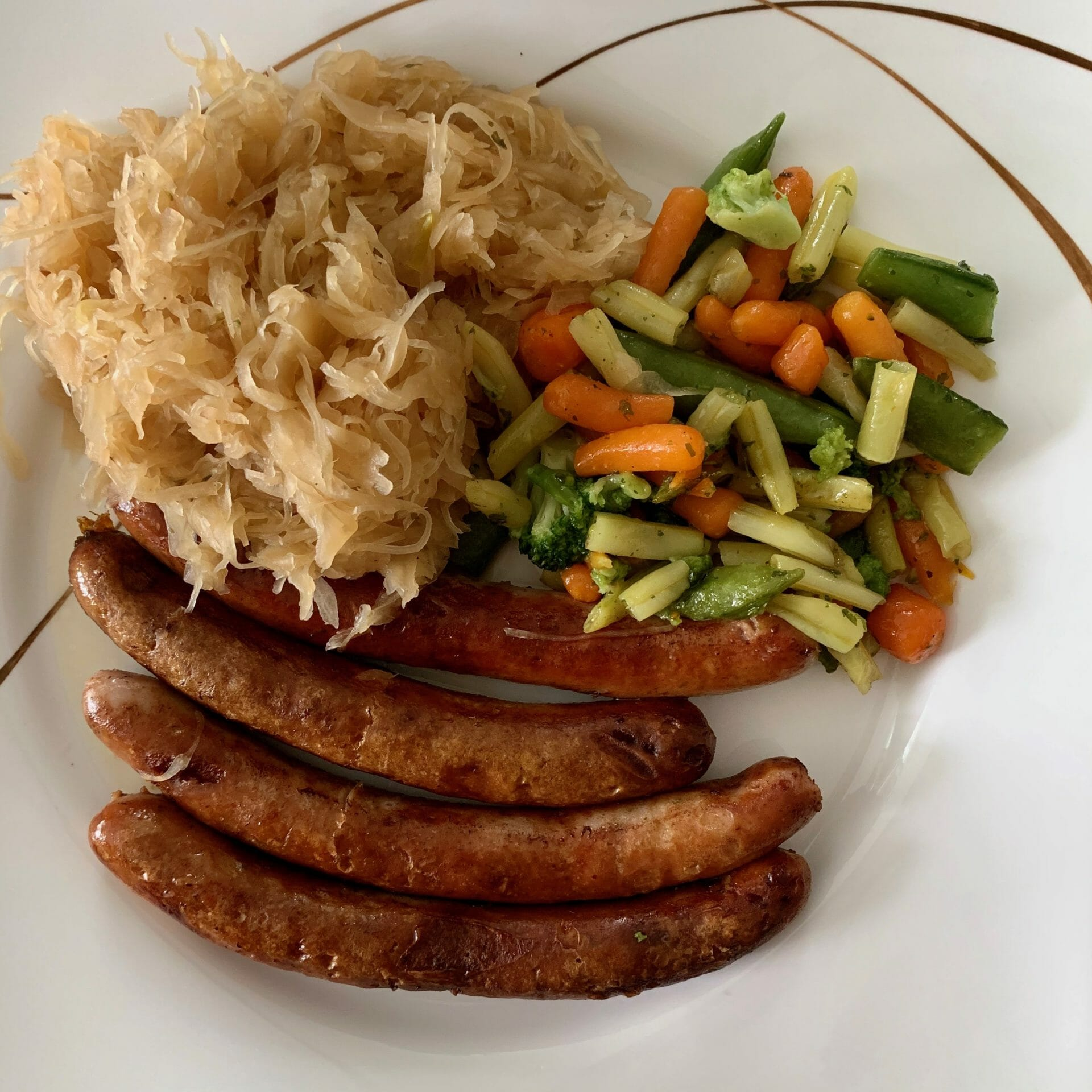 Port sausages with sauerkraut, carrots, green beans and broccoli