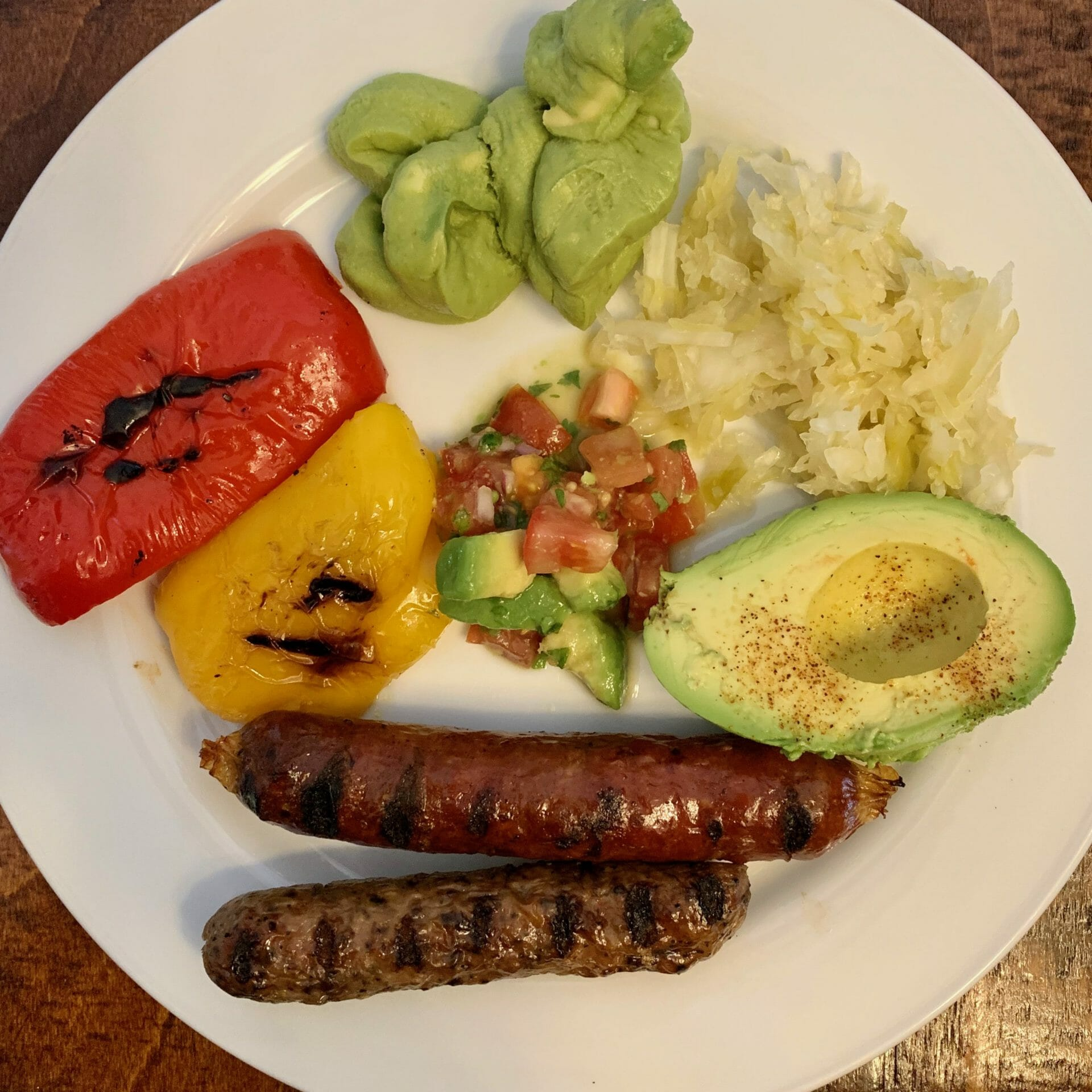 Beef and chicken sausages with grilled peppers, tomato/avocado salad, avocado, guacamole and sauerkraut