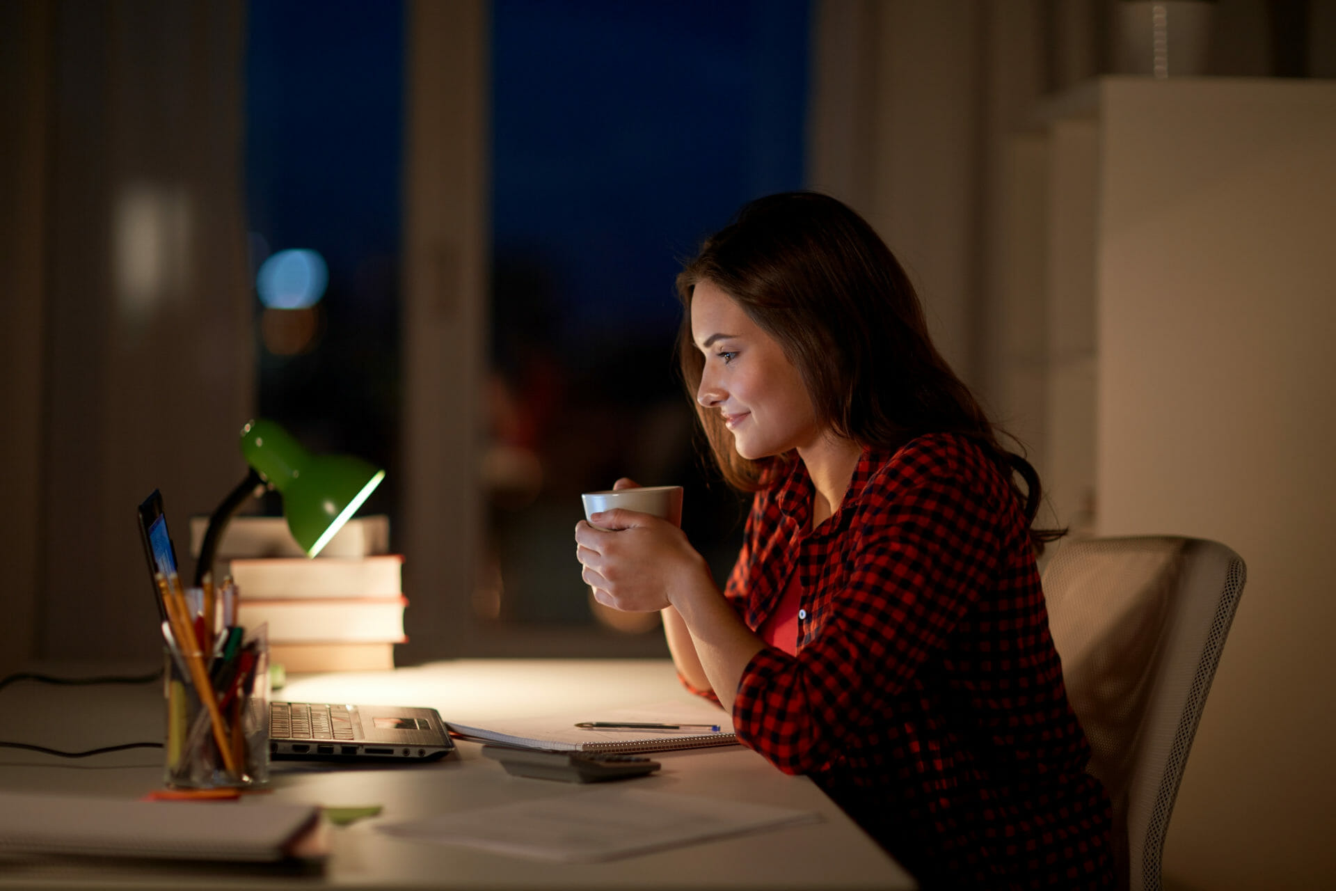 Woman drinking coffee at night