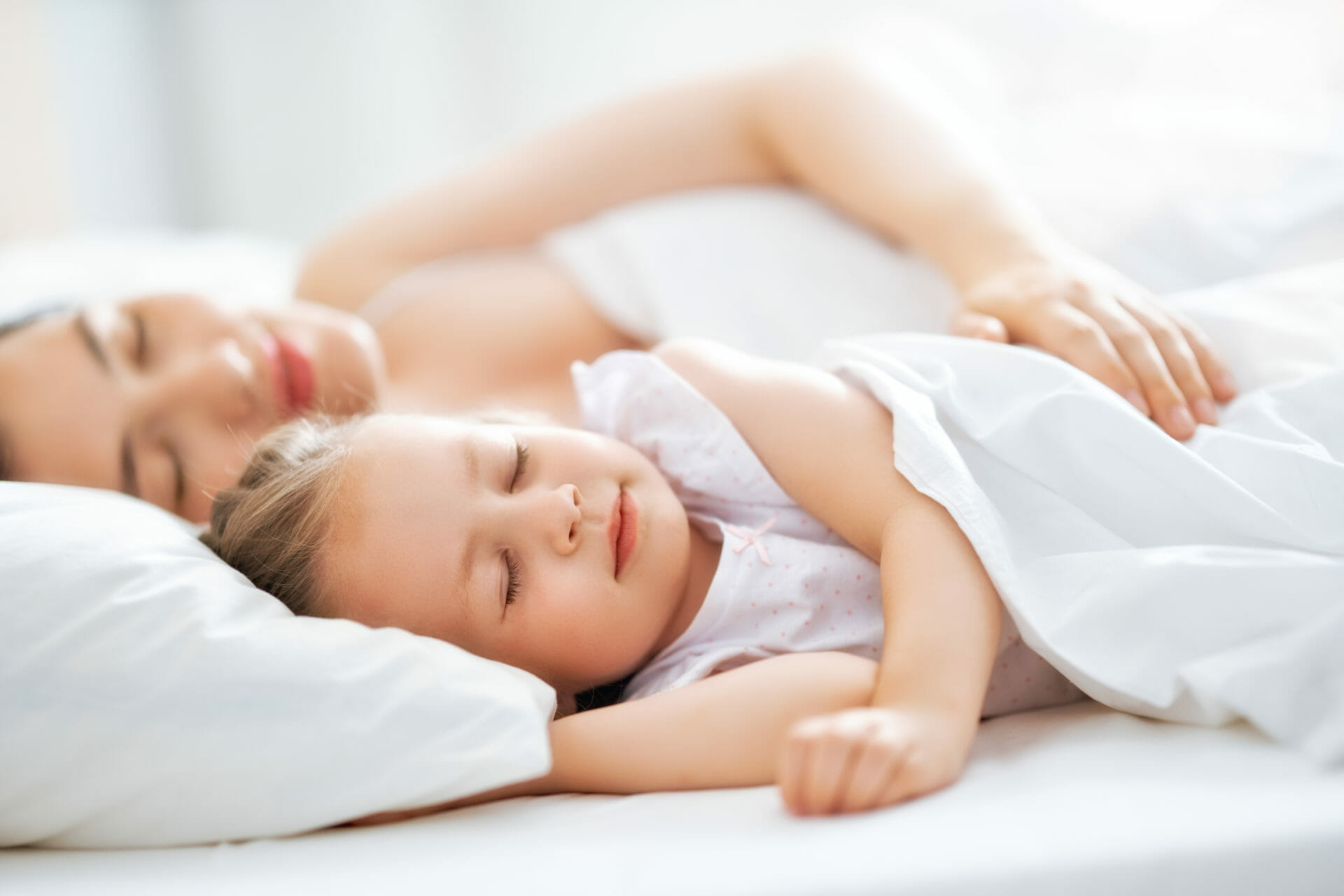Woman sharing a bed with toddler